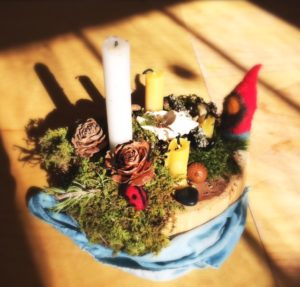 kindergarten advent garden table decoration with moss, gnome, and candle