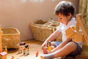 little boy playing with waldorf wooden toys